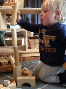 1 year old Lola stacks cylinder blocks during the first day's free play building session.