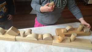 2 year old Kahlan arranges assorted shapes.