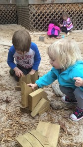 4 year old Henry (from the Hummingbird class) & 2 year old Helena build with loose parts on the playground during Block Week.